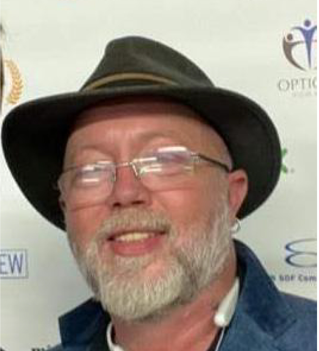 A headshot of Steven W. Allen a white male in his mid-fifties with a gray beard and blue eyes. He is wearing glasses, a black-rimmed hat, and blue jacket. He is smiling at the camera.