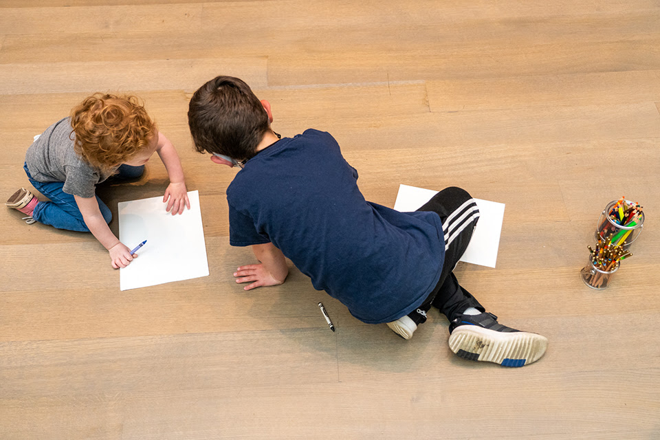 Two children laying on the ground drawing on paper